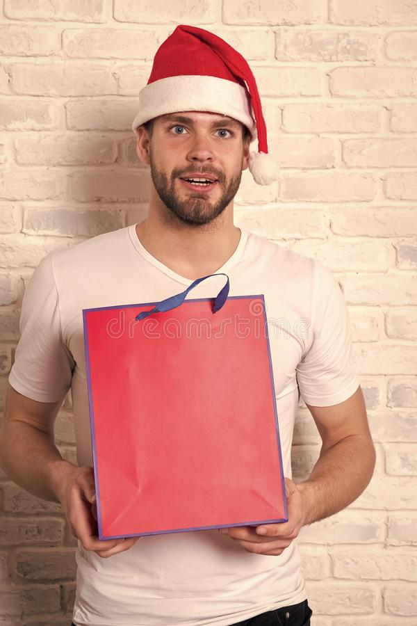 Man in santa hat hold christmas present. online christmas shopping. Happy new year, copy space. delivery christmas gifts. The morning before Xmas. happy santa royalty free stock image