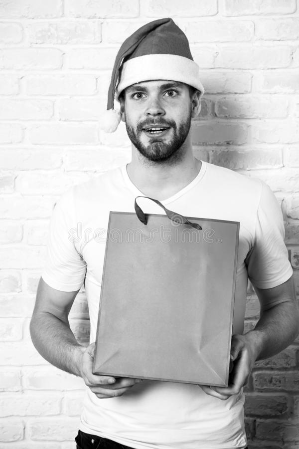 Man in santa hat hold christmas present. online christmas shopping. Happy new year, copy space. delivery christmas gifts. The morning before Xmas. happy santa royalty free stock images