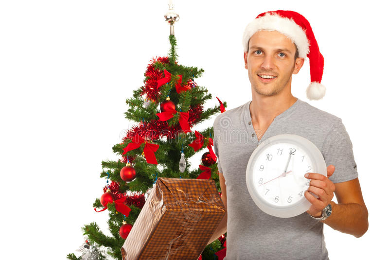 Man with Santa hat holding clock. Happy man with Santa hat holding Christmas present and clock stock photo