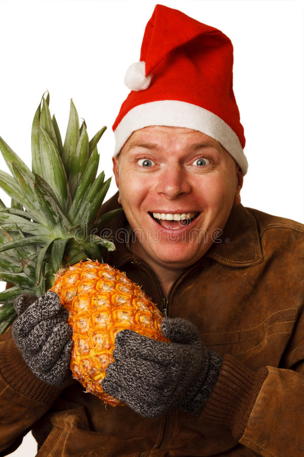 Man in Santa hat with pineapple. Man in the New Year's Eve wants to get a taste of summer sun and pineapple royalty free stock image