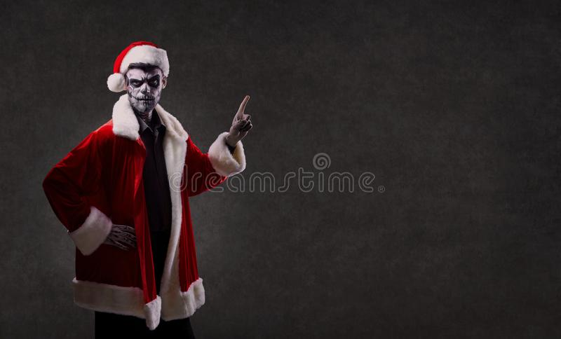 A man in Santa`s costume with a makeup skeleton on his face. royalty free stock photo