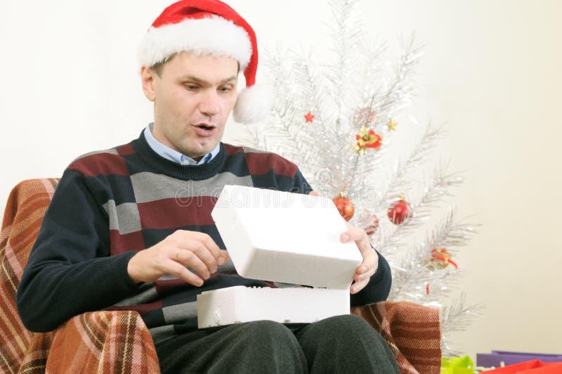 Man in Santa's hat opening Christmas gift. Man in Santa's hat opening gift box under the Christmas tree royalty free stock photo
