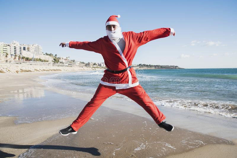 Man in a santa suit jumping on the beach. A young caucasian man in a santa suit jumps on the beach stock photo