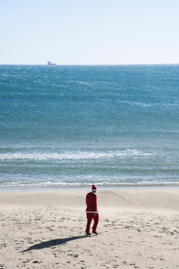 Man in a santa suit walking on the sand of a beach. Young man wearing a santa suit, seen from behind, walking on the sand of a beach, with the ocean in the stock photography