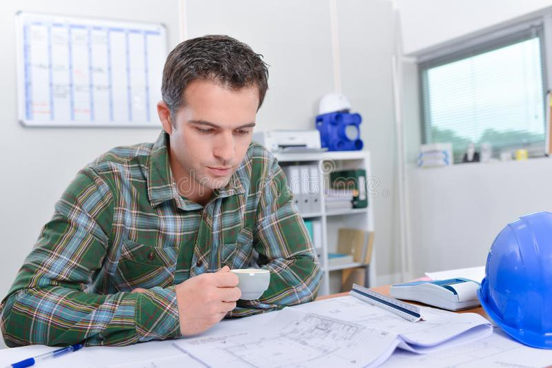 Man sat at desk looking at blueprints holding cup royalty free stock photos