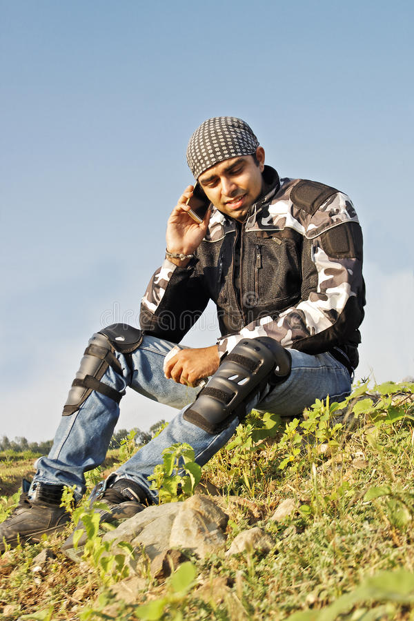 Man sat at roadside using cell phone stock photography