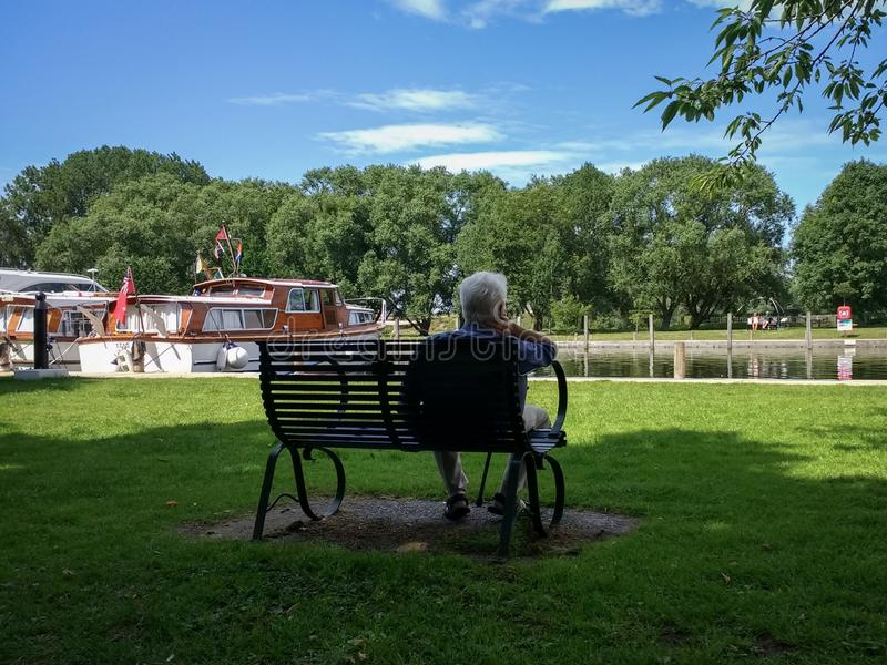 Man sat on a seat admiring the boats at Beccles Quay on the River Waveney royalty free stock photos