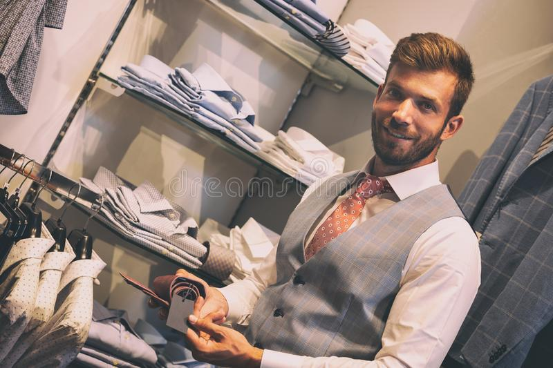 Man found tie he on  action discount at a boutique. Man satisfied with a tie, which he found on special discount at the boutique royalty free stock photos