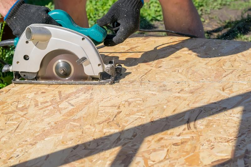A man sawing a Board with a power tool, chips fly. In all directions. Construction, wood processing royalty free stock image