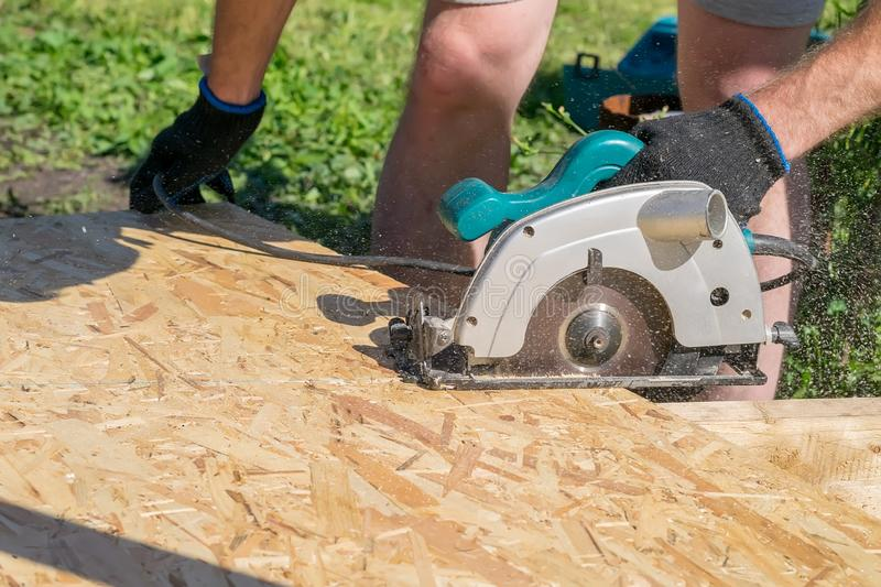 A man sawing a Board with a power tool, chips fly. In all directions. Construction, wood processing stock photos