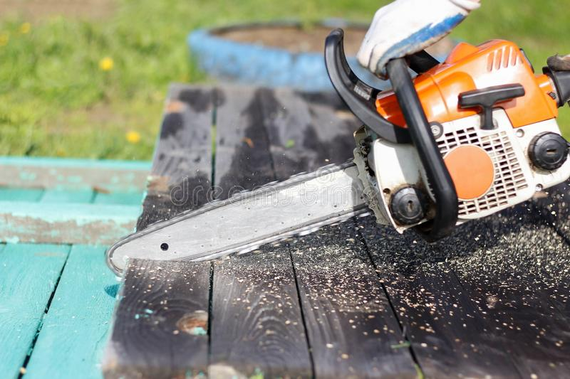 Man sawing boards with a chainsaw. Close up royalty free stock images