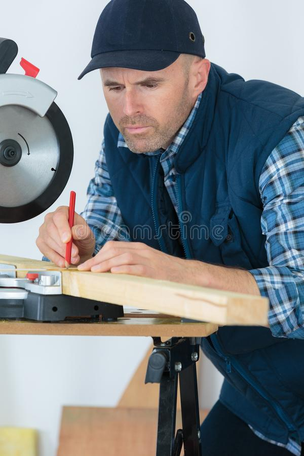 Man sawing with modern circular saw in workshop stock photos