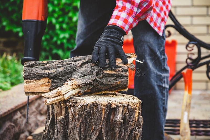Man sawing piece of wood on stump power saw stock photography