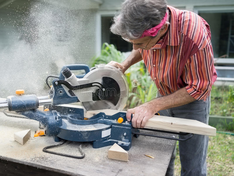 Man Sawing Wood with Sliding Compound Miter Saw. Closeup of mature man sawing lumber with sliding compound miter saw outdoors, sawdust flying around stock photos