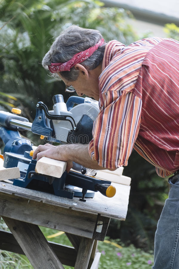 Man Sawing Wood with Sliding Compound Miter Saw. Closeup of mature man sawing lumber with sliding compound miter saw outdoors, sawdust flying around stock photo