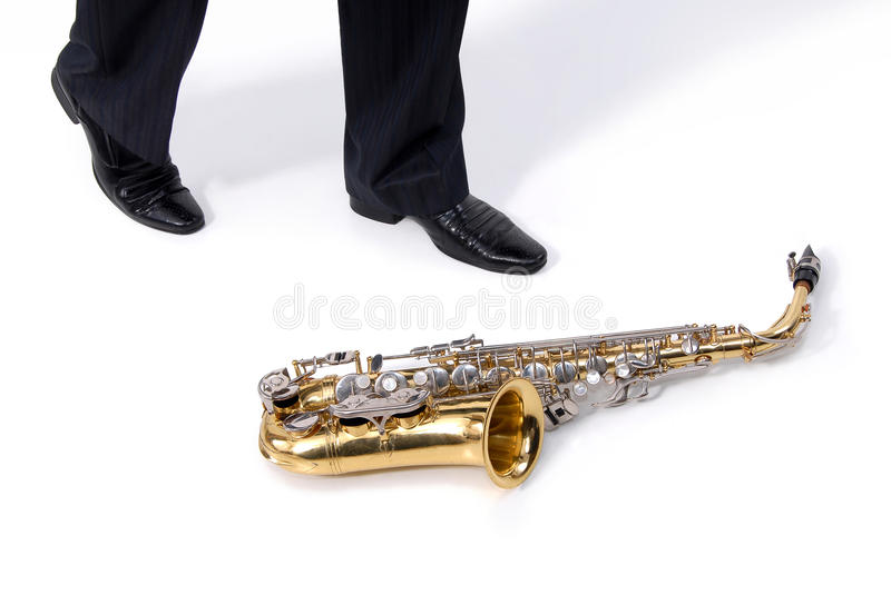 Man and saxophone. Man' foots and saxophone on the floor stock photo
