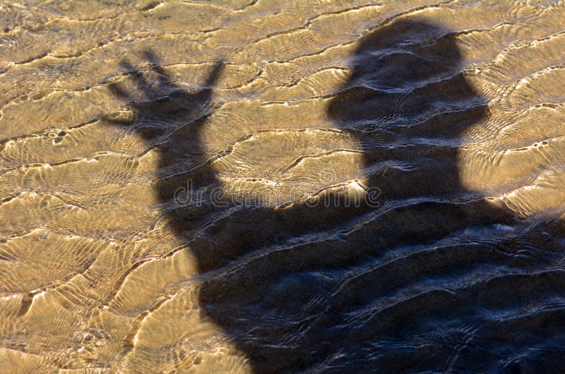 Man say hello/ goodbye. Silhouette of man say hello/ goodbye on sea water and seabed background texture stock images