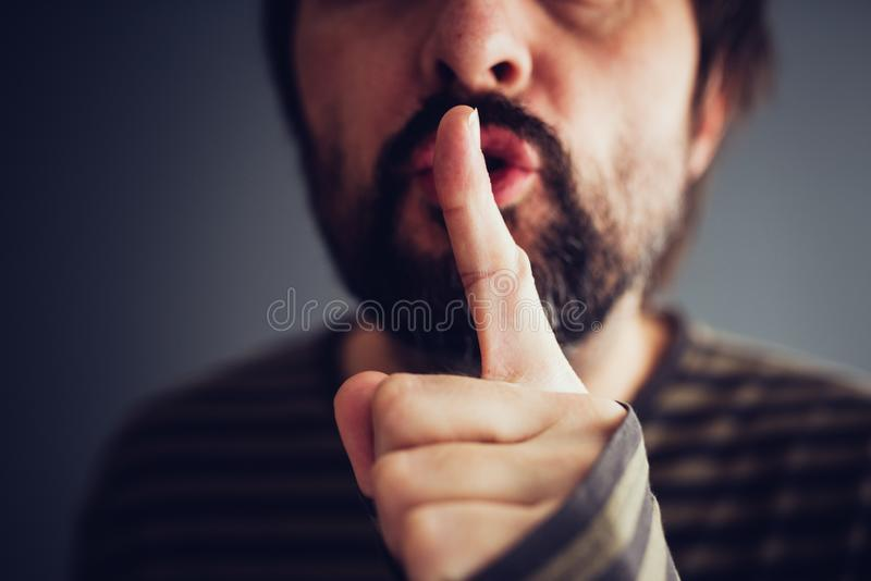 Man saying hush or be quiet. With finger on lips, close up with selective focus stock photography