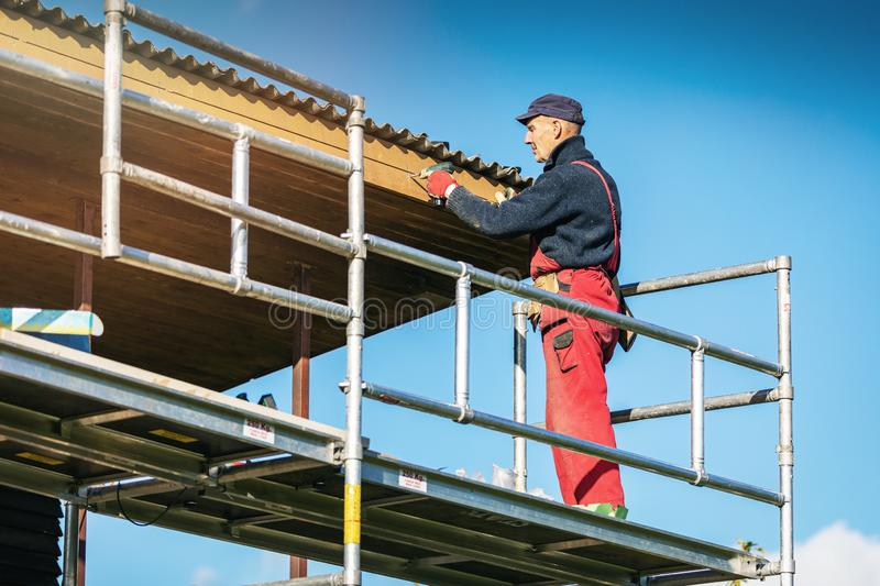 Man on scaffolding installing new wooden planks on house roof eaves stock photography