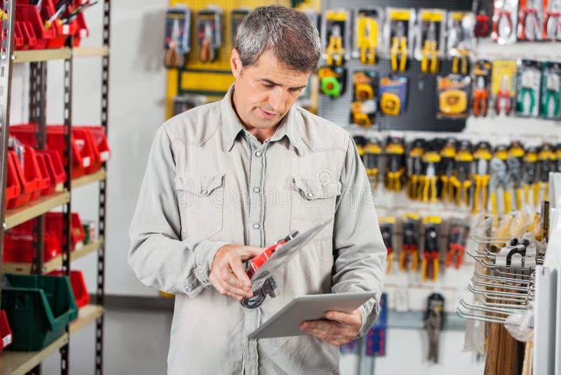 Man Scanning Product Through Digital Tablet. Mature man scanning product through digital tablet in hardware store stock image