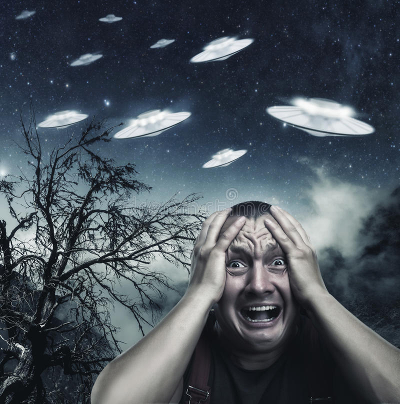 Man scared by UFO. Scared by UFO man screaming at night in the forest royalty free stock photo
