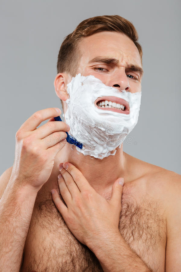 Man scares to shave over gray background. Handsome young man scares to shave isolated on the gray background royalty free stock images