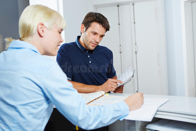 Man scheduling appointment at reception of dentist stock photo
