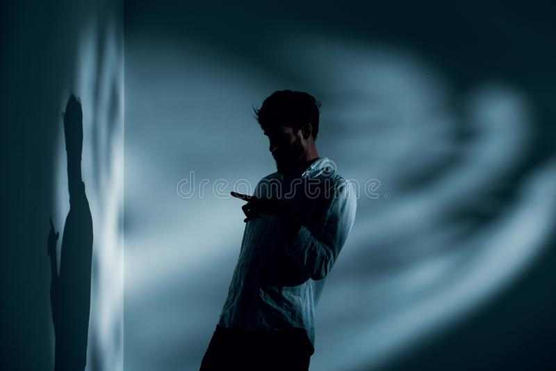 Man with schizophrenia standing alone in dark interior talking to his shadow, photo with copy space. On the wall stock image