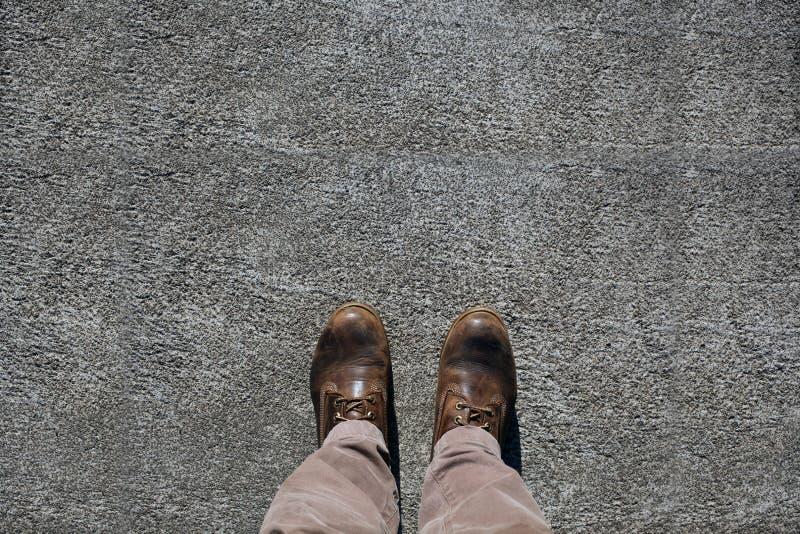 Man schoenenmening van hierboven over concrete bestrating met grote exemplaarruimte voor uw tekst stock fotografie