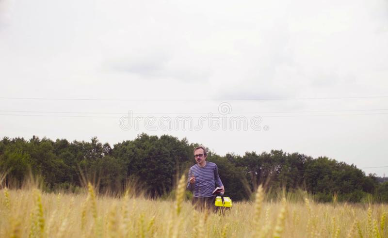 The man scientist ecologist walking through the wheat field royalty free stock photo