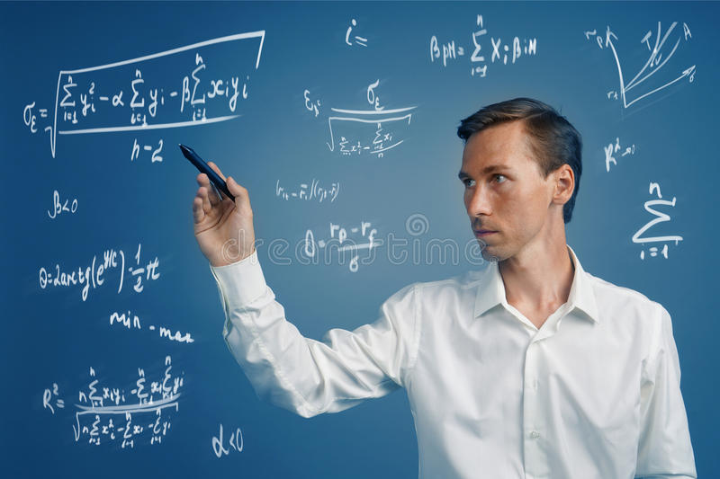 Man scientist or student working with various high school maths and science formulas. Man scientist or student working with various high school maths and stock images