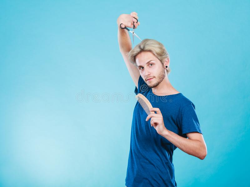 Man with scissors and comb creating new coiffure. Style and fashion. Young trendy male hairstylist barber with new idea of look changing. Blonde guy with stock photo
