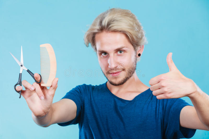 Man with scissors and comb creating new coiffure. Style and fashion. Young trendy male hairstylist barber with new idea of look changing. Blonde guy with stock images