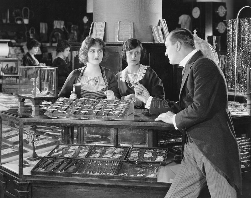 Man scolding saleswomen. (All persons depicted are no longer living and no estate exists. Supplier grants that there will be no model release issues stock photos