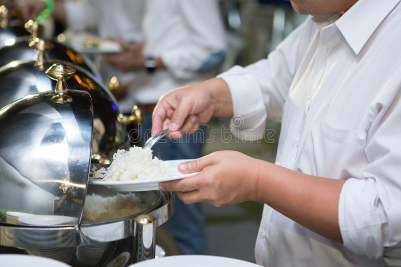 Man are scooping food from chafing dishes on the table at the banquet. Man are scooping food from chafing dishes on the table at the luxury banquet royalty free stock photo