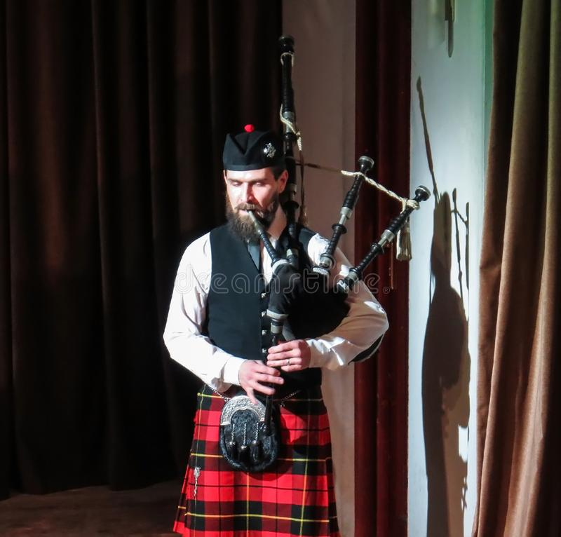 A man in Scottish national attire with a musical instrument royalty free stock image
