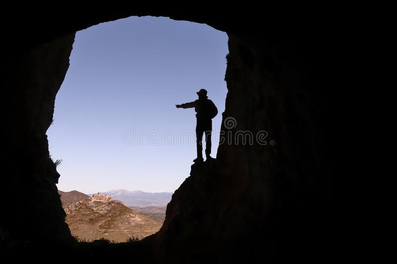 A MAN SCOUT WITH A HAT IN A CAVE POINTING TO A CASTLE IN THE DISTANCE royalty free stock image