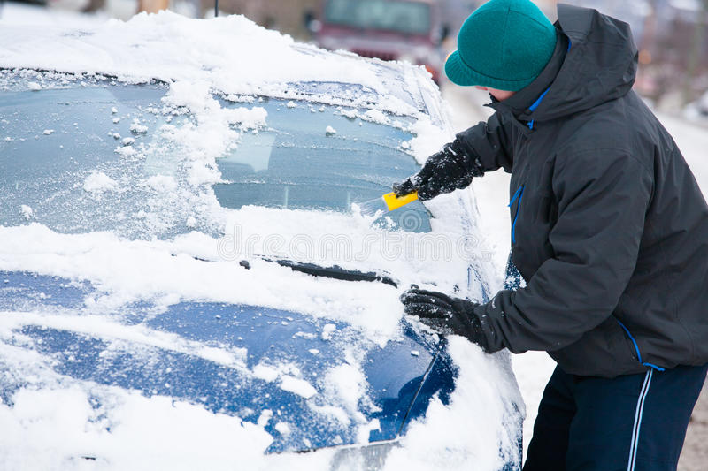 Man Scraping Ice off Car. Man scraping ice and snow off of the windshield of his car after a winter snowstorm royalty free stock images