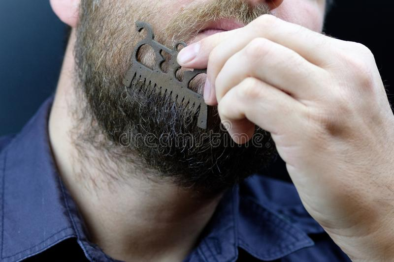A man scratches his beard with an old beard comb. A rare comb made of metal of the 17th century royalty free stock photos