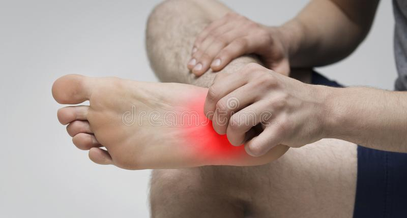 Man scratching bare foot with red rush stock image