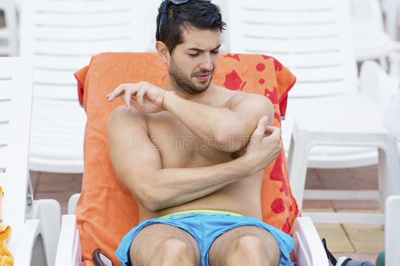 Man scratching after a mosquito bite. Young man with itching after a mosquito bite on a pool.Man scratching at itchy skin stock images