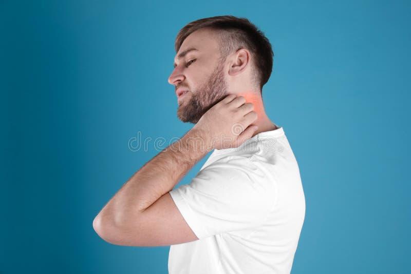 Man scratching neck. Allergy symptoms. Man scratching neck on color background. Allergy symptoms stock photos