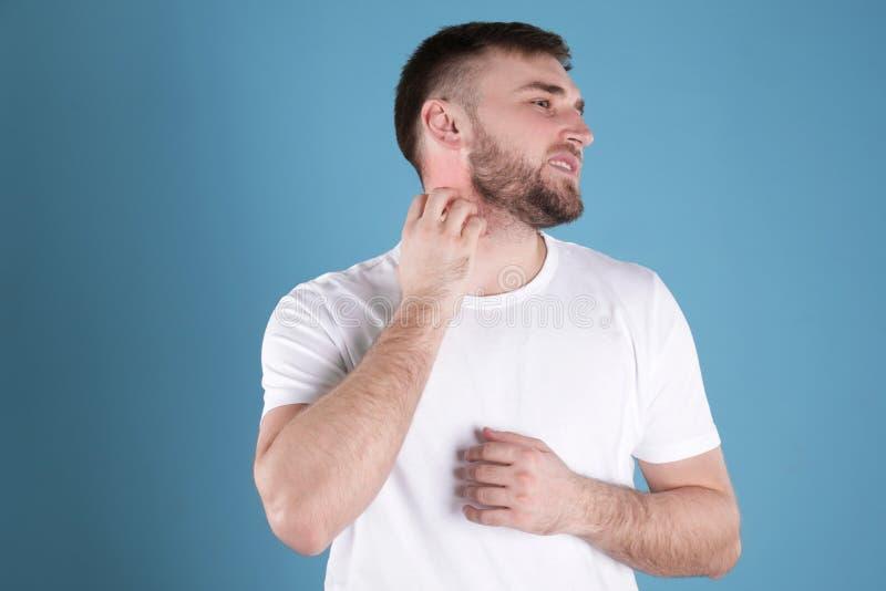 Man scratching neck. Allergy symptoms. Man scratching neck on color background. Allergy symptoms royalty free stock photography