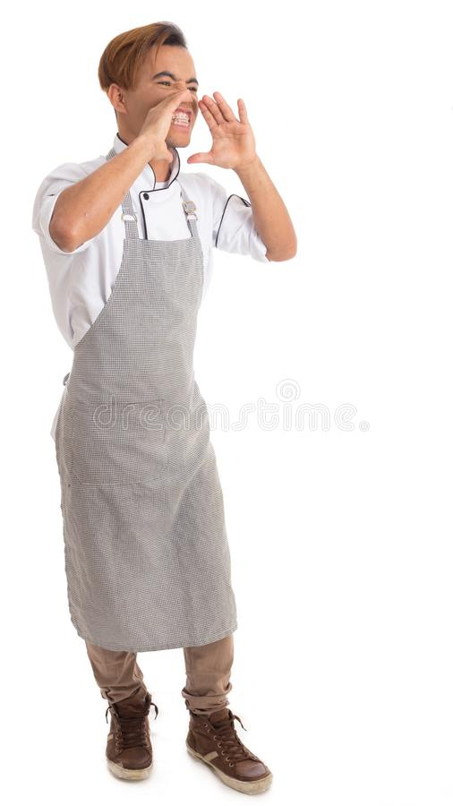 Man is angry and screams. Black cook wears apron. Isolated on white background.. stock image