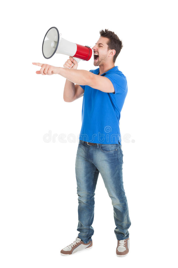 Man Screaming Into Bullhorn While Pointing Away. Full length of aggressive young man screaming into bullhorn while pointing away over white background royalty free stock photos