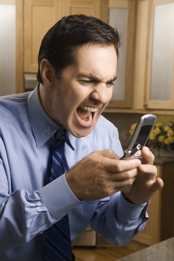 Man screaming at cellphone royalty free stock photography
