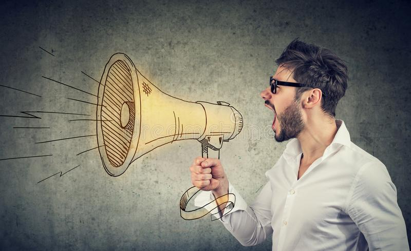 Man screaming into loud speaker. Side view of man in eyeglasses and white shirt spreading news and making announcement with loudspeaker stock image