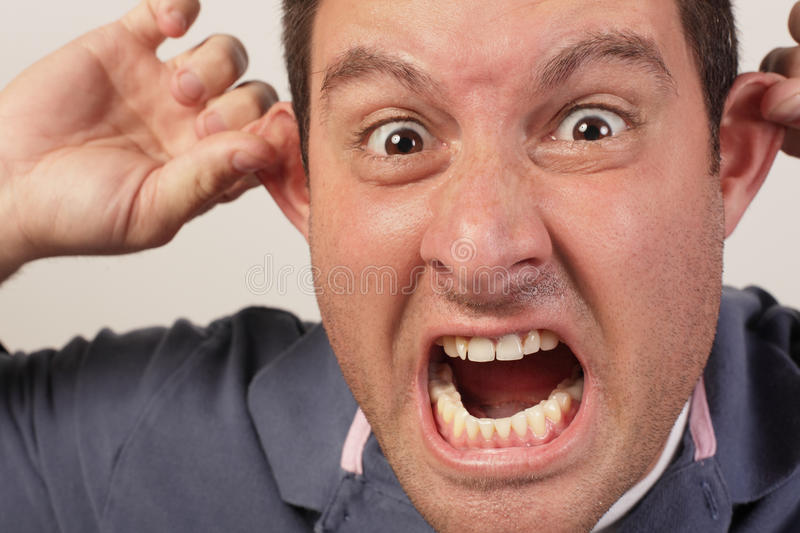 Man screaming and pulling his ears royalty free stock photo