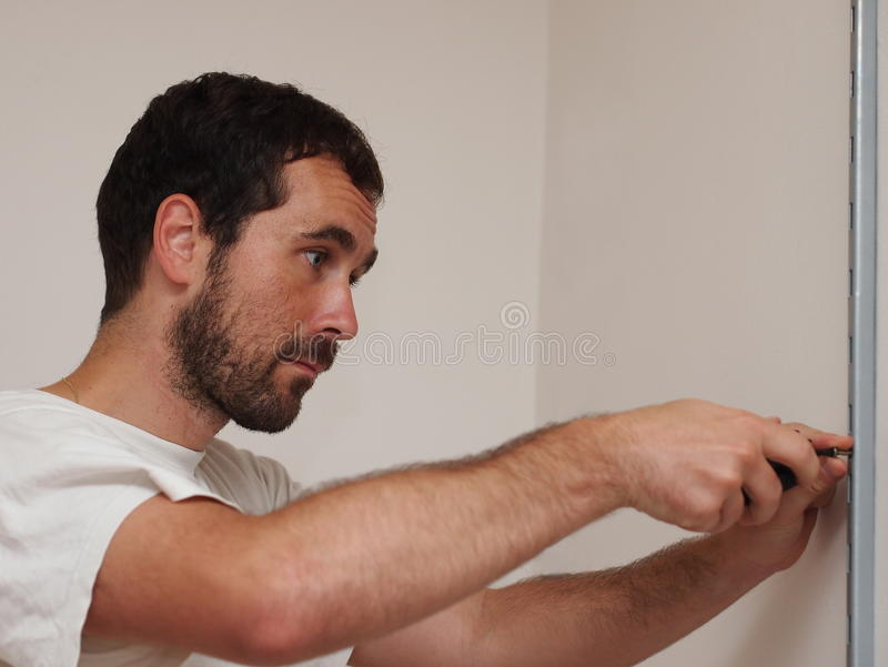 Man with a screwdriver. Black-haired man screwing a metal bar to a white wall stock photography