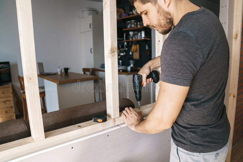 Man with a screwdriver in his hand fixes a wooden structure for a window in his house. Repair yourself. stock photo